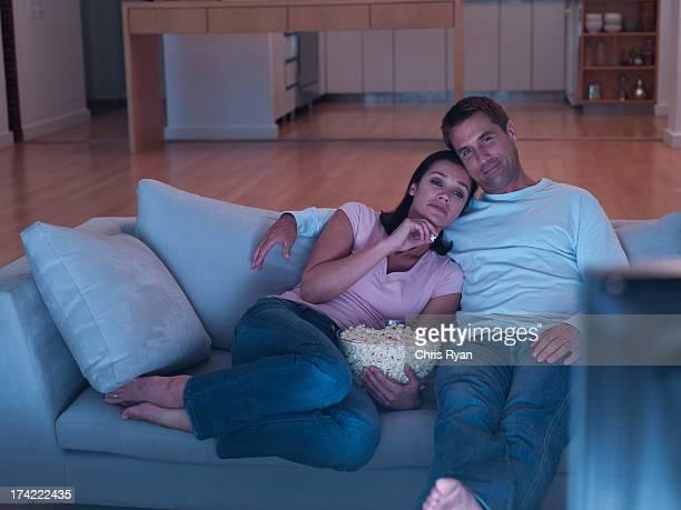 frau und mann auf sofa vor dem fernseher mit popcorn - abenddämmerung stock-fotos und bilder