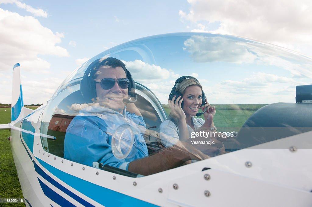 Woman and man pilot looking at camera, preparing for flying : Stock Photo