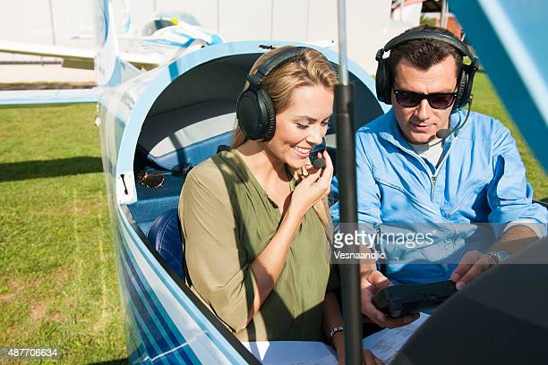 Woman and man pilot looking at map, preparing for flying