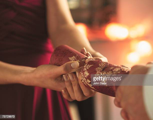 'Woman and man pulling Christmas cracker, mid section'