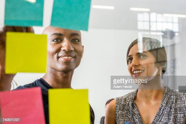 woman and man reading adhesive notes in office - non binary gender stock pictures, royalty-free photos & images