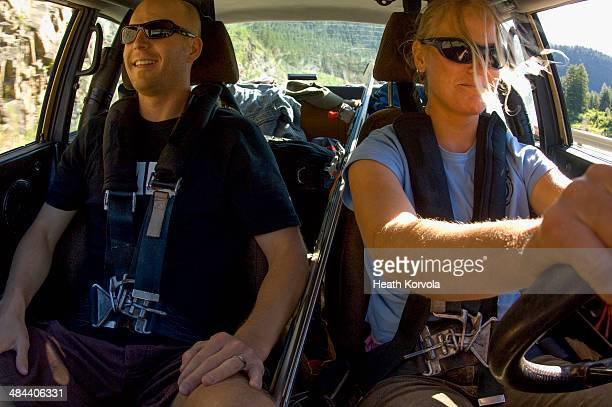 Woman and man riding in sports car in summer.