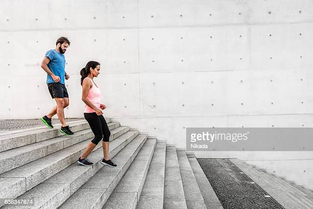 woman and man running down steps together