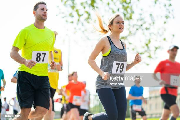 woman and man running marathon - marathon stock pictures, royalty-free photos & images