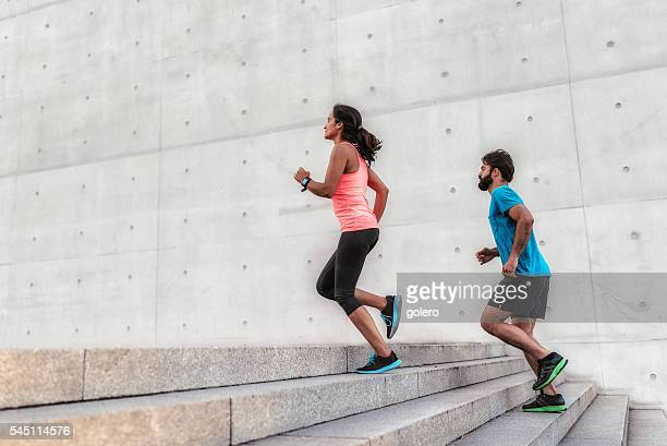 woman and man running up stone stairway outdoors