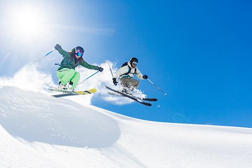 Woman and man skiing and jumping 660685390