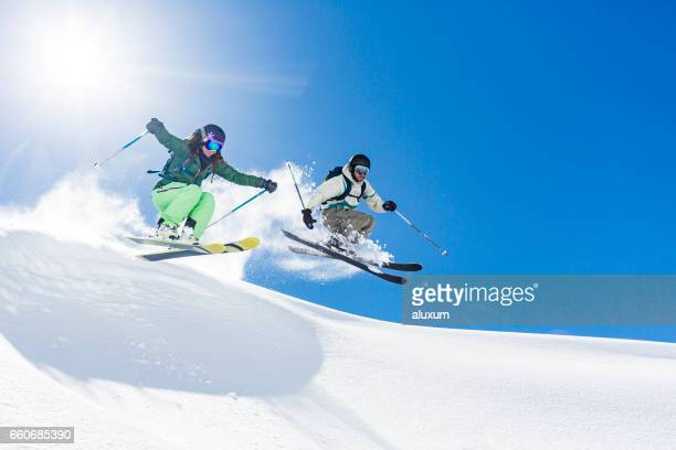 Woman and man skiing and jumping