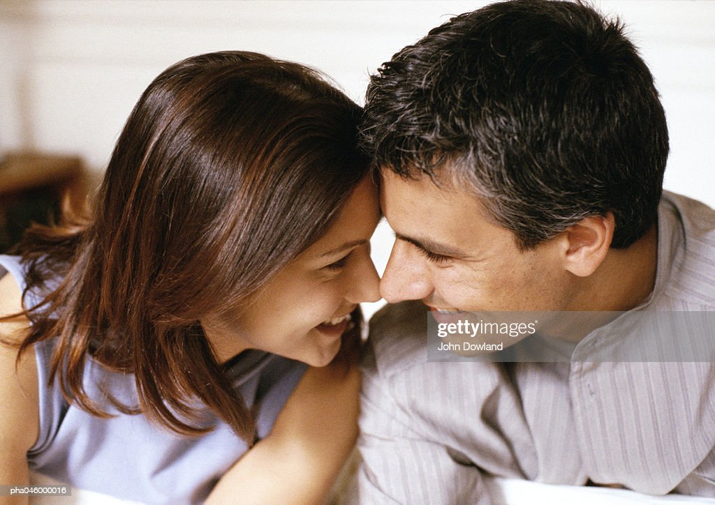 Woman and man smiling, foreheads and noses touching, side view, close-up : Stockfoto