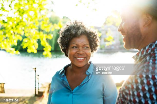 woman and man smiling together next to river - mature adult stock pictures, royalty-free photos & images