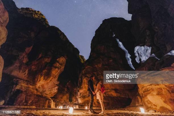 woman and man standing near petra by night - monumento foto e immagini stock