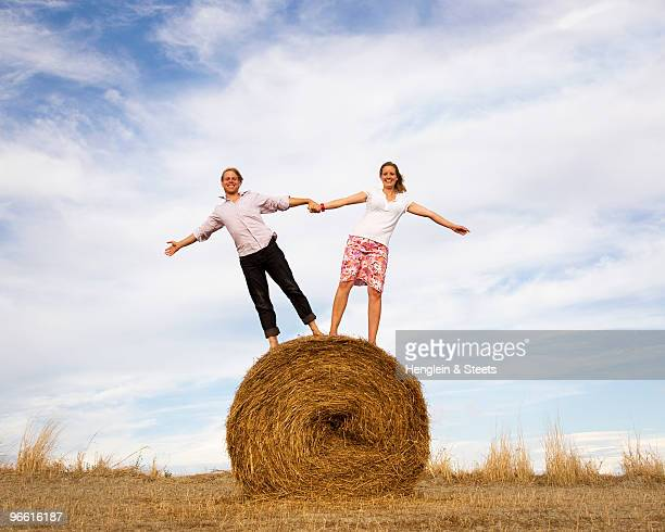 woman and man standing on hay bale