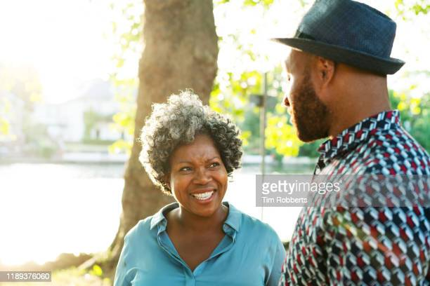 woman and man talking next to river - flirting stock pictures, royalty-free photos & images