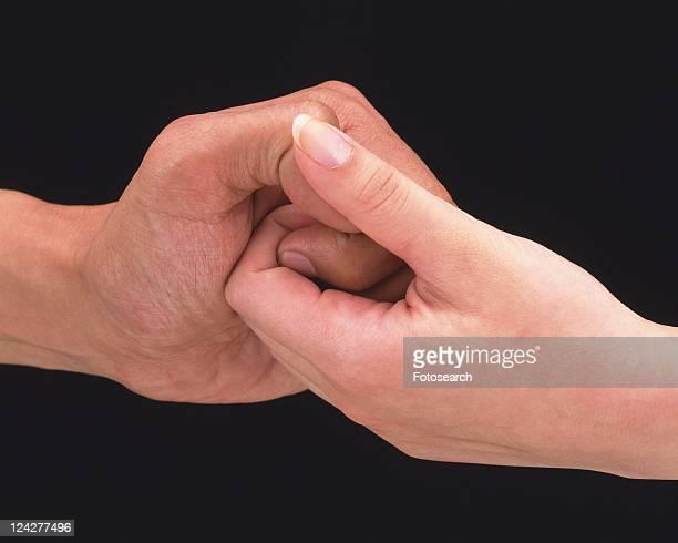 Woman and man thumb wrestling