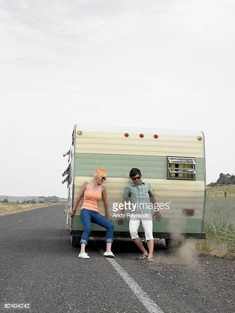 woman and man trying to push trailer