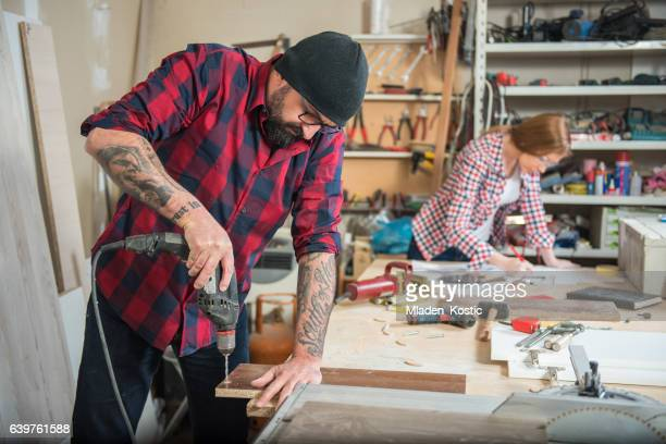 Woman and man using power tools in a carpenter workshop