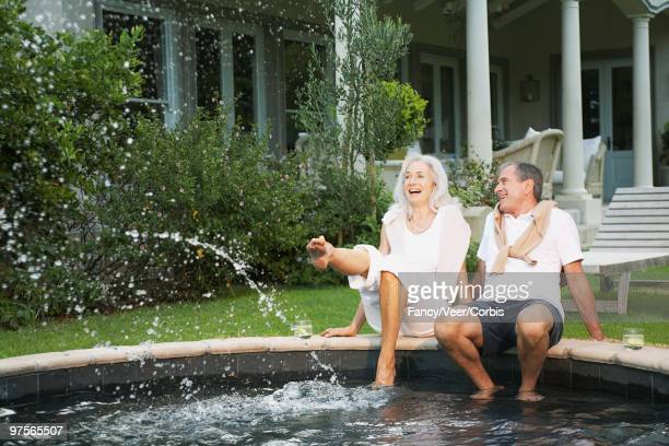 woman and man wading in swimming pool - old lady feet stock pictures, royalty-free photos & images