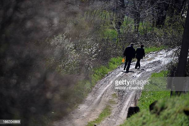 A woman and man walk down a road near the homes of yesterdays shooting victims in the village of Velika Ivanca 40 kilometres south of Belgrade on...