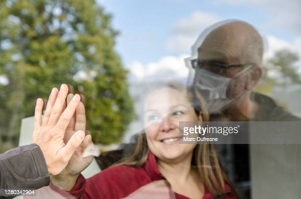woman and man wearing face mask touching hands through window - photographed through window stock pictures, royalty-free photos & images