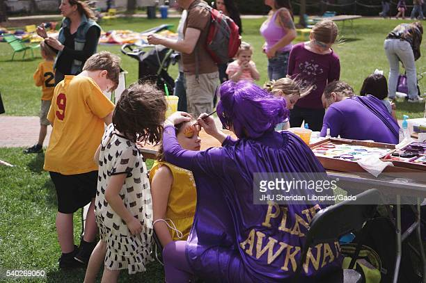 Woman and man wearing purple superhero costumes, including cape and wig, paint designs onto the faces of young children during Spring Fair, a...