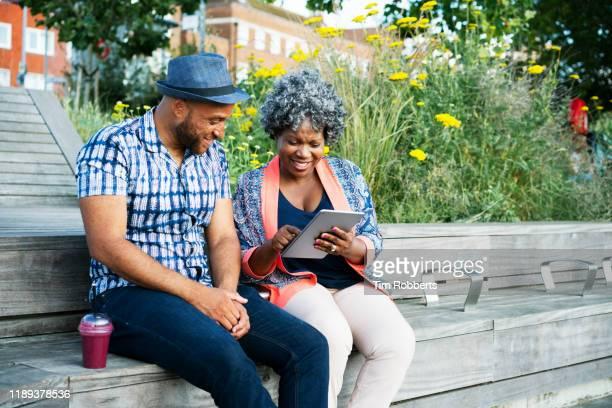 woman and man with digital tablet outside - websurfen stock-fotos und bilder