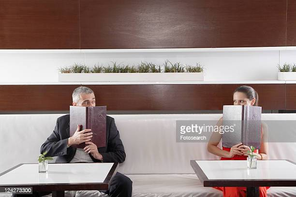 Woman and man with menus over their face looking at each other