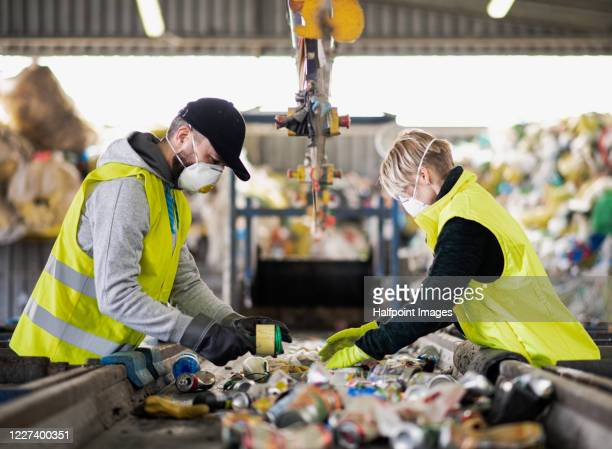 woman and man workers with protective face masks on landfill, waste management and environmental concept. - factory stock pictures, royalty-free photos & images