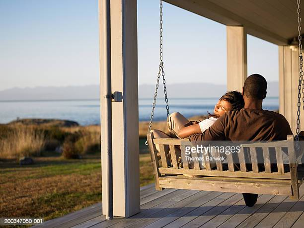 Woman and mature man sitting on swing chair on porch
