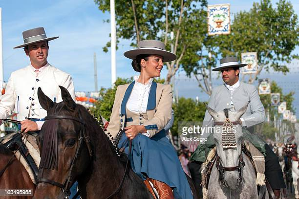 Woman and men riding horses during the Seville April Fair or the Feria de abril de Sevilla, Spain