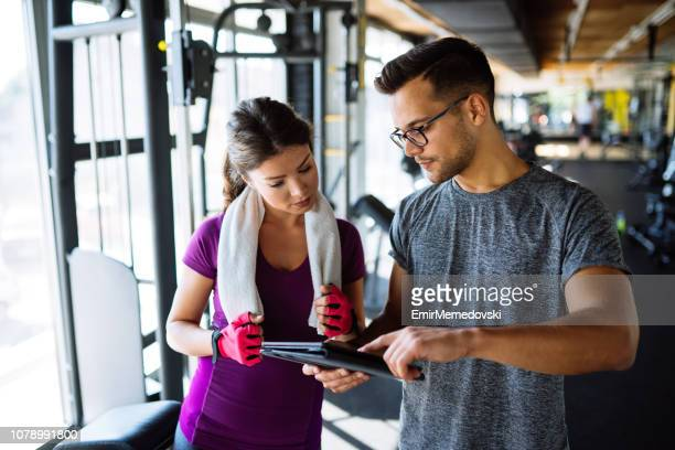 woman and personal trainer making exercise plan in gym - instructor stock pictures, royalty-free photos & images