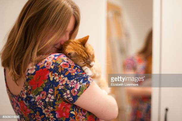 woman and pet cat hugging - floral pattern dress stock pictures, royalty-free photos & images