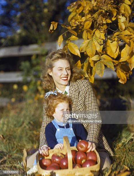 Woman and red haired girl with a basket full of red apples in the fall USA