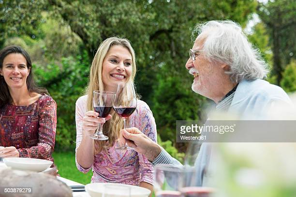 Woman and senior man clinking wine glasses on a garden party