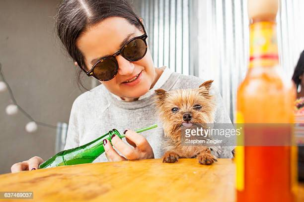 Woman and small dog sharing a soda