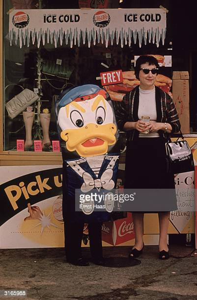 A woman and somebody dressed as 'Donald Duck' by a PepsiCola stand during Mardi Gras New Orleans Louisiana