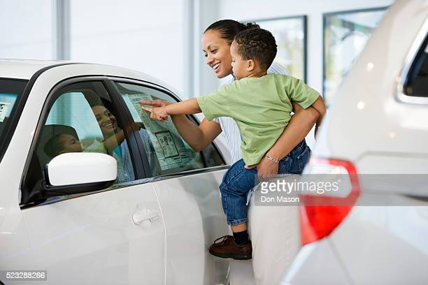 woman and son looking at car's sticker price - car shopping stock pictures, royalty-free photos & images