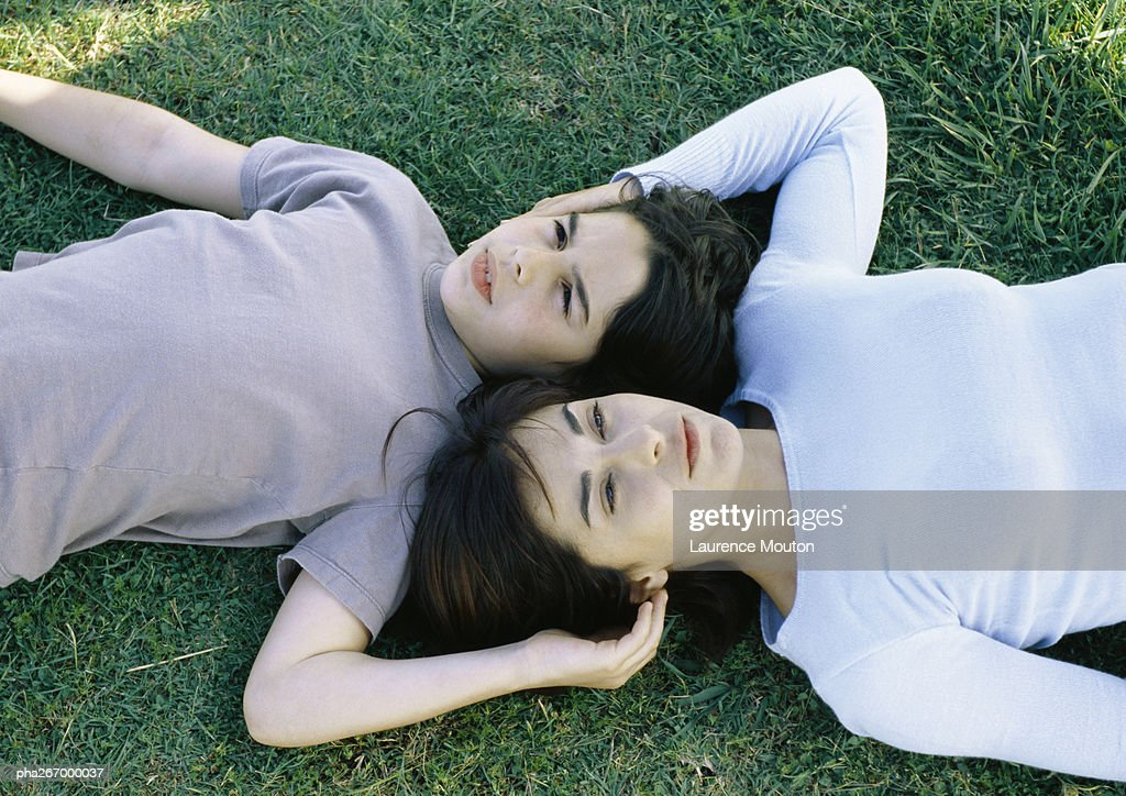 Woman and son lying on grass head to head : Stockfoto