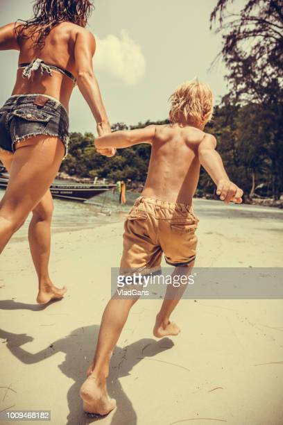 Woman and son running along the beach