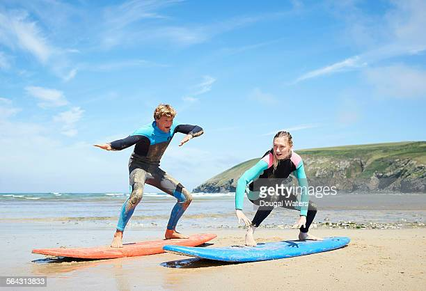 woman and surf instructor on beach - dougal waters stock pictures, royalty-free photos & images