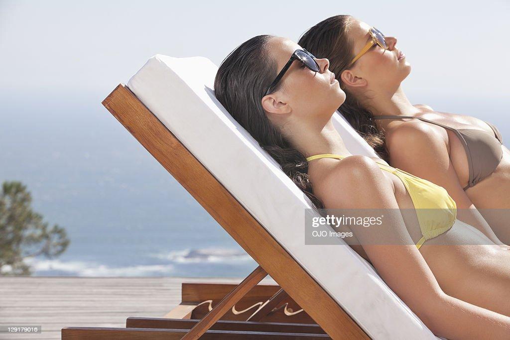 Woman and teenage girl in bikini sunbathing on beach : Stock Photo