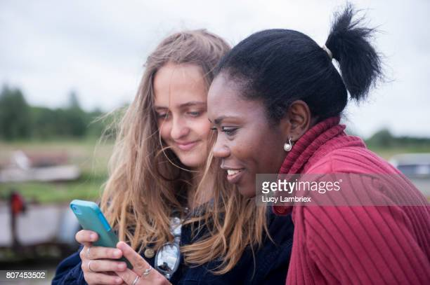Woman and teenage girl looking at smartphone