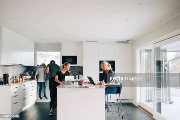Woman and teenage girl using laptops while man boy standing in kitchen at home