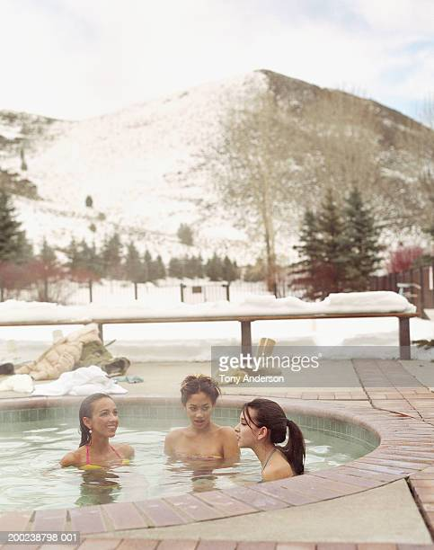 woman and teenage girls (14-17) soaking in outdoor hot tub - girls in hot tub stock photos and pictures