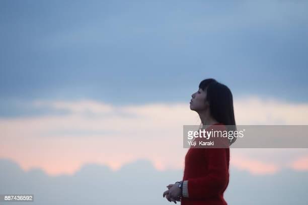 女性と夕焼け雲