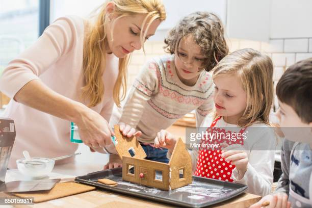 A woman and three children creating a baked gingerbread house.