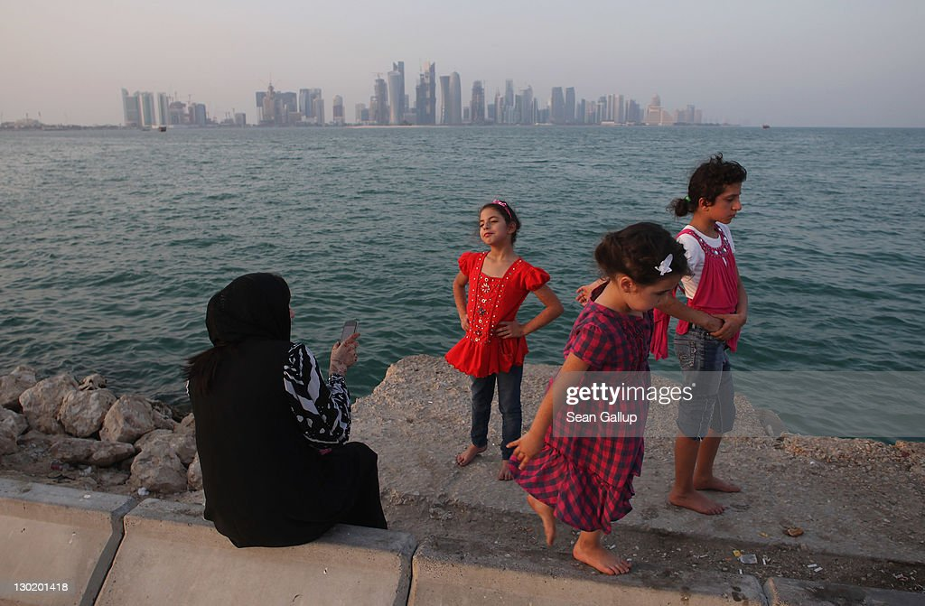 A woman and three children enjoy the waterfront along the Persian Gulf across from new, budding financial district skyscrapers on October 24, 2011 in Doha, Qatar. Qatar will host the 2022 FIFA World Cup football competition and is slated to tackle a variety of infrastructure projects, including the construction of new stadiums.