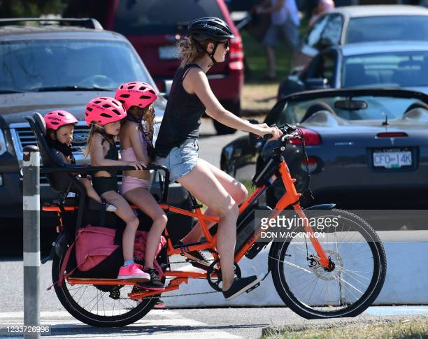 Woman and three children go on a cooling bike ride on a scorching hot day, in Vancouver, British Columbia, June 29, 2021. - Schools and Covid-19...