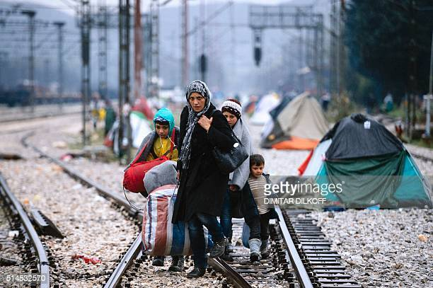 A woman and three children walk on railway tracks connecting Greece with western Europe at the GreekMacedonian border near the Greek village of...