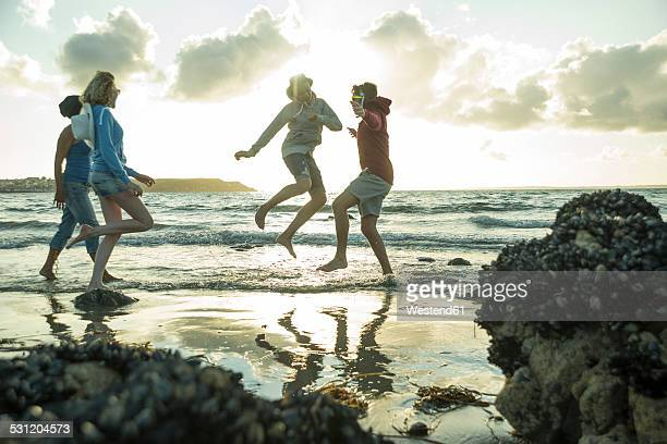 Woman and three teenagers having fun on the beach by sunset