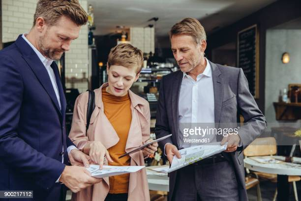 Woman and two businessmen discussing plans in a cafe