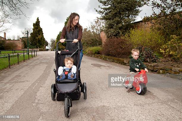 woman and two children in  park - three wheeled pushchair stock pictures, royalty-free photos & images